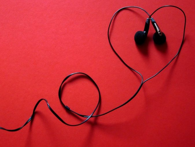 headphones in a heart shape on solid red background
