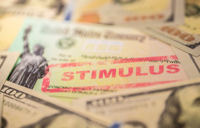 "Blurry photo of 100 dollar bills with United States Treasury check and ""Stimulus"" stamped in red."