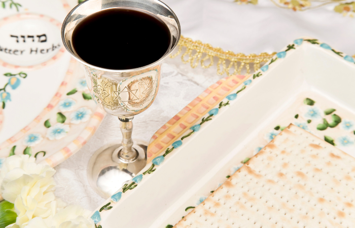Close up of silver goblet filled with red wine and ceramic dish with matza
